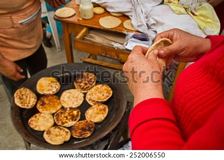 CUENCA, AZUAY, ECUADOR - JUNE 20, 2010 : Indigenous woman making corn tortillas in a Cuenca local market - stock photo