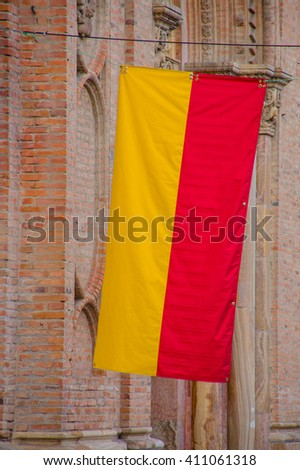 Cuenca, Ecuador - April 22, 2015: Closeup yellow and red Cuenca flag hanging down from pole attached to brick building - stock photo