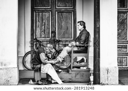CUENCA, ECUADOR - JAN 9, 2015: Unidentified Ecuadorian man cleans the other man shoes. 71,9% of Ecuadorian people belong to the Mestizo ethnic group