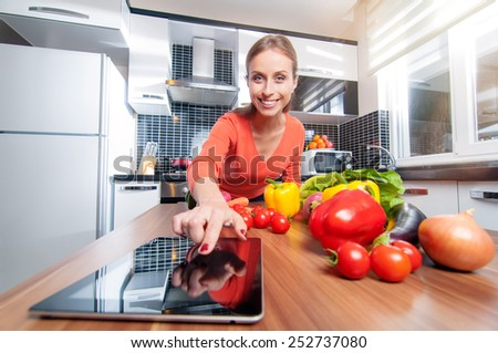 Cuisine and technology. Smiling Woman In Kitchen Following Recipe On Digital Tablet - stock photo