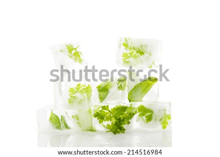 Culinary aromatic cooking herbs basil and parsley frozen in ice cubes isolated on white background. Fresh healthy cooking.  - stock photo