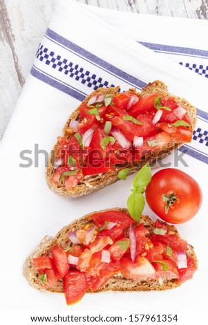 Culinary bruschetta eating, rustic style. Bruschetta bread with fresh tomatoes on white cloth, top view. Delicious mediterranean eating.  - stock photo