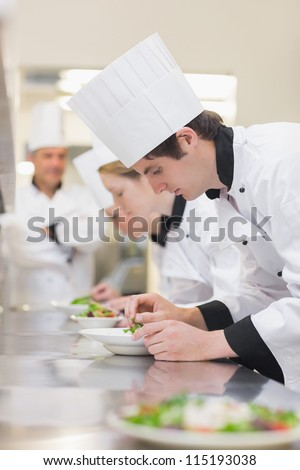 Culinary class preparing salads as teacher is supervising - stock photo