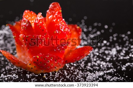 Culinary ornament from ripe strawberry on a black plate. Close up, horizontal shot, small depth of sharpness - stock photo