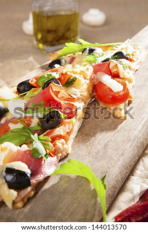 Culinary pizza eating. Pizza with prosciutto, ham, black olives, herbs on wooden cutting board on brown background. Traditional pizza background.