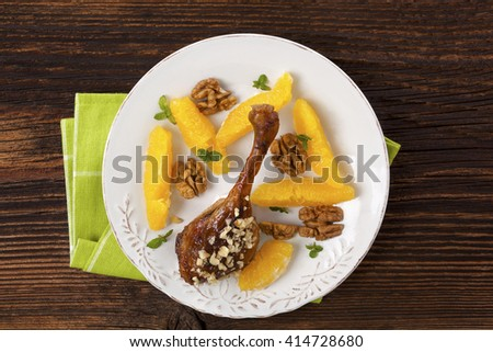 Culinary roast duck with oranges and nuts on plate on wooden table. Flat lay, top view. Delicious festive eating.  - stock photo