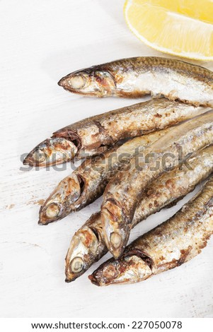 Culinary seafood eating. Grilled sardines on plate with lemon on white wooden background, top view. - stock photo