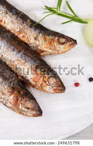 Culinary seafood eating. Grilled sardines on wooden background with fresh herbs and lemon. Culinary mediterranean eating.  - stock photo