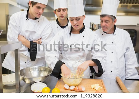 Culinary students learning how to mix dough in kitchen - stock photo
