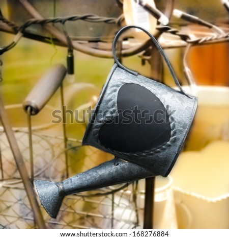 Cultivate your Love! Valentines day background. Watering can with heart shape and other garden equipment.