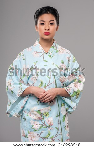 Cultural spirit. Young attractive Asian beauty standing over grey backgorund with her hands on her belt - stock photo