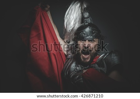 Culture, Praetorian Roman legionary and red cloak, armor and sword in war attitude - stock photo