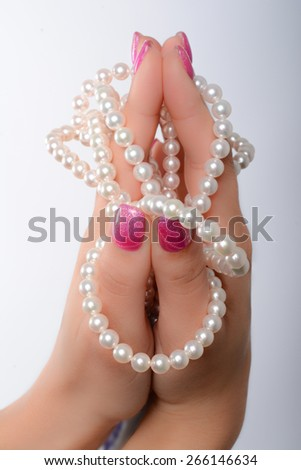 cultured pearls presented with nails painted pink - stock photo