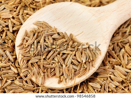 cumin seeds and wooden spoon as background