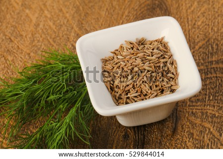 Cumin seeds heap on the wood background