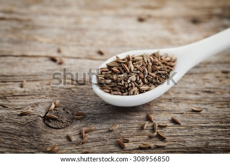 Cumin seeds or caraway in white spoon on wooden board - stock photo