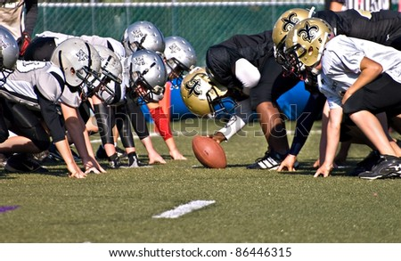 CUMMING, GA - OCTOBER 8: Several unidentified age 11 to 13-year-old  boys at the line of scrimmage, the Raiders vs the Saints, on October 8, 2011 in Cumming, GA. - stock photo