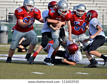 CUMMING, GA/USA - SEPTEMBER 8: Unidentified boys blocking and tackling during a football game. Two teams of 7th grade boys September 8, 2012 in Cumming GA. The Wildcats  vs The Mustangs.