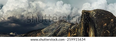 Cumulonimbus clouds above the ridge of Half Dome cliffs at Yosemite National Park before sunset - stock photo