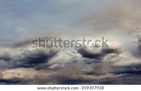 Cumulostratus  clouds in a blue Australian sky in mid summer are   wreathed in smoke haze from a raging bush fire burning out of control  fanned by strong winds in the forest in summer . - stock photo