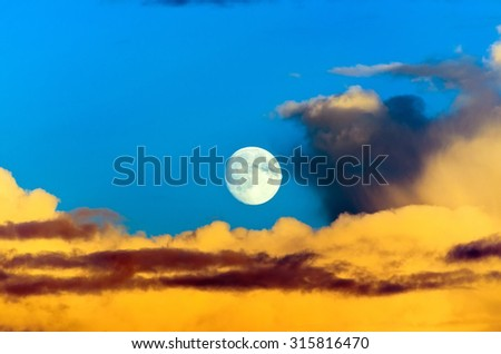 Cumulus clouds at sunset the moon full moon night - stock photo