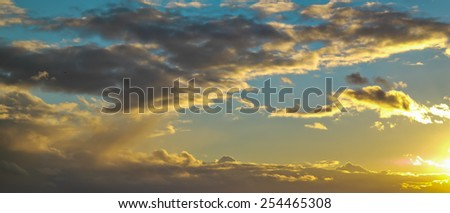Cumulus clouds in the blue sky at sunset - stock photo