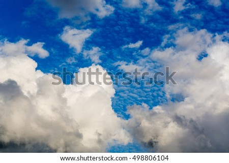 Cumulus clouds white and dark on blue sky