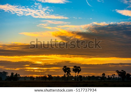 Cumulus sunset clouds with sun setting down on dark background.orange cloud sky and blue sky. Beautiful sky.
