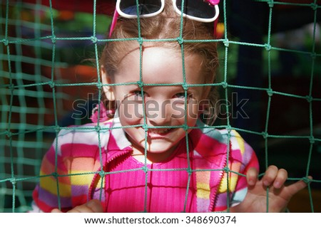 Cunning  girl hid behind the green grid  - stock photo