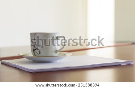 Cup and a stack of papers on his desk - stock photo