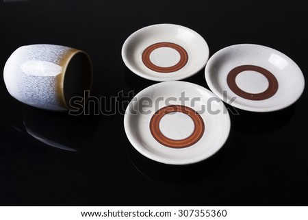 Cup and bowls of traditional Japanese pottery on black background