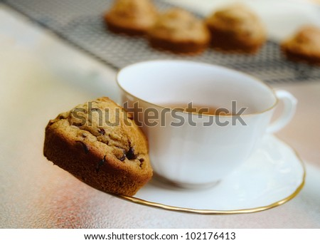 Cup and saucer with muffin on plate with muffins on cooling rack in background.