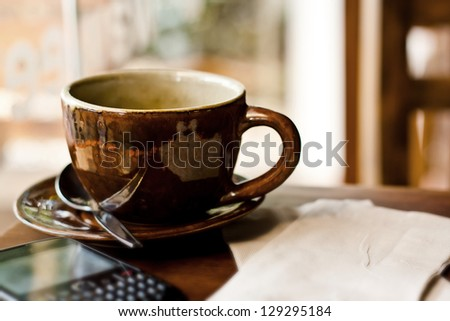 Cup and smart phone on wood table in cafe - stock photo
