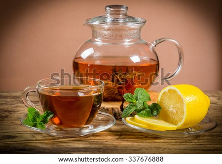 Cup and teapot of green tea with lemon and mint on old wooden desk - stock photo