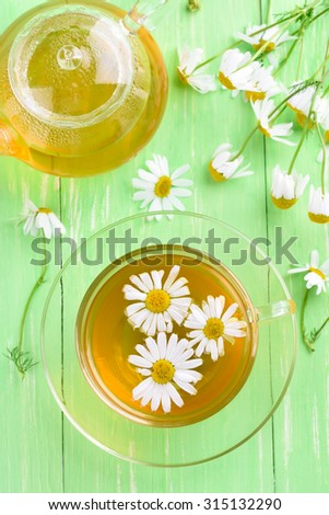 Cup and teapot of herbal tea with fresh flowers on wooden table, top view - stock photo