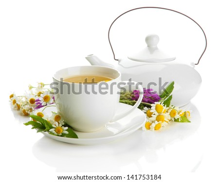 Cup and teapot of herbal tea with wild flowers and mint, isolated on white