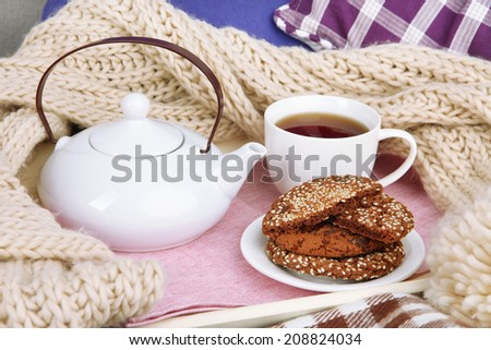 Cup and teapot with cookies on tray and scarf on bed close up - stock photo