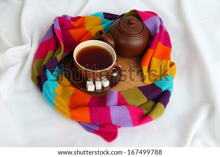 Cup and teapot with scarf on fabric background - stock photo