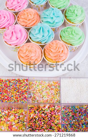 Cup cake and Candy sprinkles on white background - stock photo