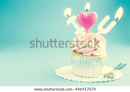Cup cake with birthday candle vintage background - stock photo