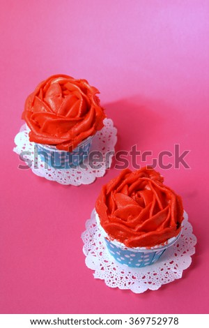 cup cake with red buttercream on pink red background - stock photo
