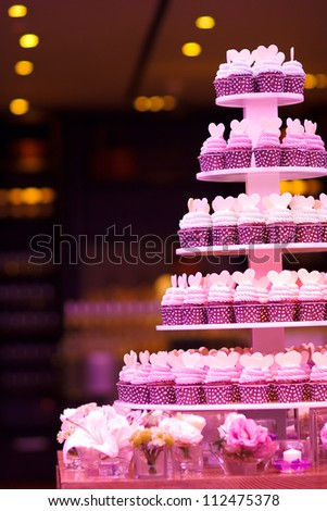 Cup cakes in wedding party with pink lighting - stock photo