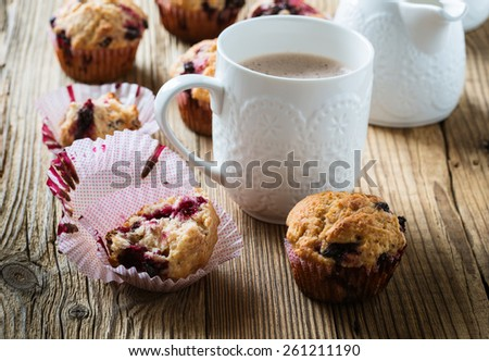 Cup cocoa with milk and homemade black berry muffins. Muffins with black currant for healthy breakfast on rustic wooden table