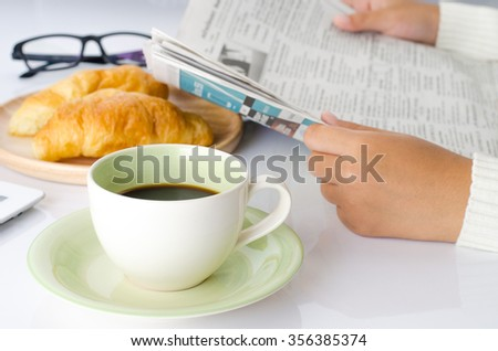 cup coffee on the desk and reading newspaper. - stock photo