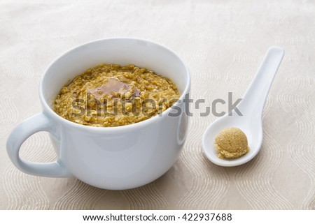 cup filled with oatmeal and drizzle of maple syrup, with a ball of brown sugar on the side