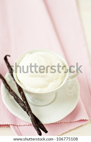 Cup filled with whipped cream with vanilla pods