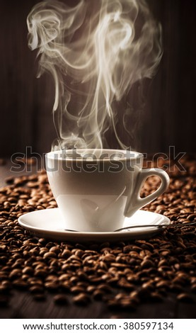 Cup fragrant coffee on beans background with spoon - stock photo