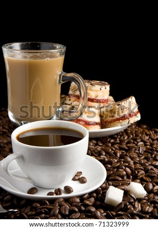 cup full of coffee and cakes beans isolated on black background - stock photo