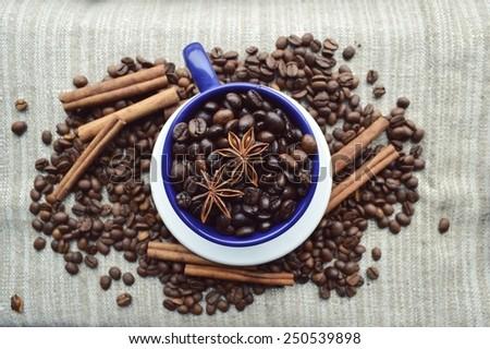 cup full of coffee beans, cinnamon sticks, star anise, closeup - stock photo
