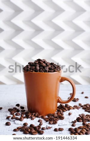 Cup full of coffee beans on light background
